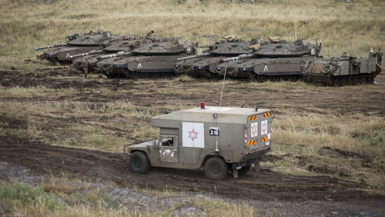 An Israeli military ambulance drives past tanks in the Israeli-controlled Golan Heights, near the border with Syria.