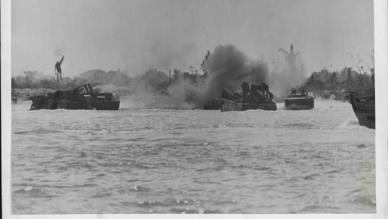 Driving into the beach at Peleliu Island in the face of heavy mortar fire, Coast Guard manned landing craft deliver men and supplies.