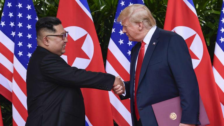 Kim Jong-un and Donald Trump shake hands.