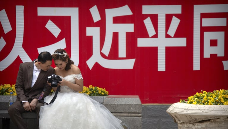 A bride and groom look at photos on the back of a camera near a propaganda slogan with the name of Chinese President Xi Jinping in Beijing.