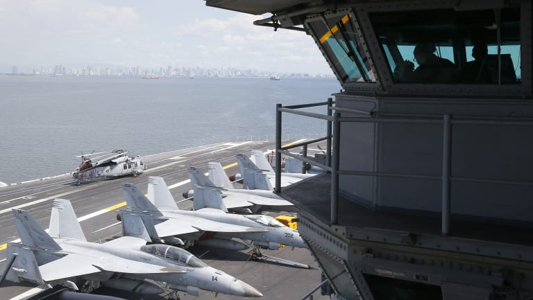 US Navy officers operate on the flight deck control tower as military aircraft sit on the flight deck of the USS Carl Vinson.