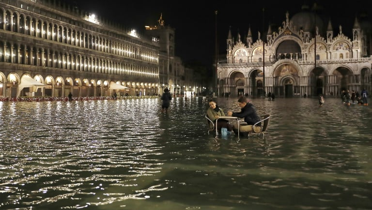 Rising seas: People sit in a flooded St. Mark's Square in Venice, Italy, as high tides inundated the city in March 2018.