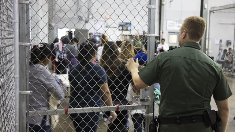 A US Border Patrol agent watches as people who\'ve been taken into custody related to cases of illegal entry into the United States, stand in line at a facility in McAllen, Texas.