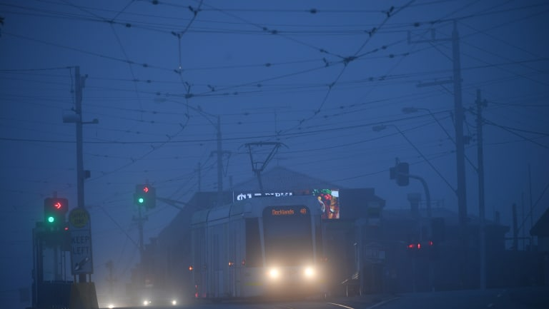 A tram passes through a foggy street in Kew early on Monday morning.