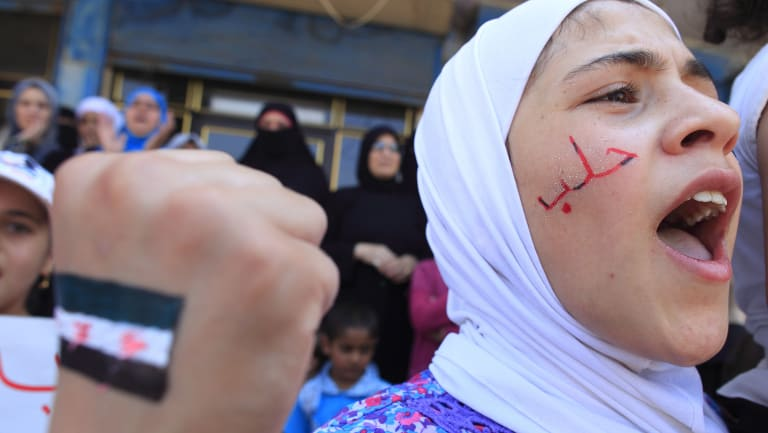 """A girl with """"Aleppo"""" written on her face shouts slogans during an anti-government demonstration in Bennish, on the outskirts of Idlib province, in August 2012."""