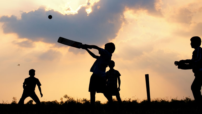Boys play cricket against a cloudy sunset in India.
