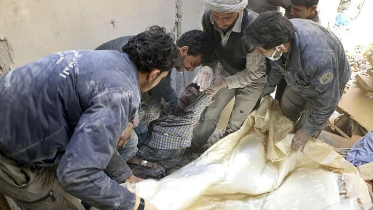 White Helmet rescuers carry a victim after airstrikes and shelling hit in Ghouta, a suburb of Damascus on Wednesday.