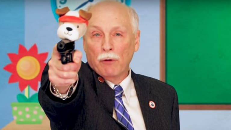 Philip Van Cleave, president of the Virginia Citizens Defence League, explains the use of 'Puppy Pistol' to children in a satirical video orchestrated by Sacha Baron Cohen.