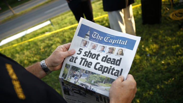 A reader holding a copy of The Capital a day after the shooting.