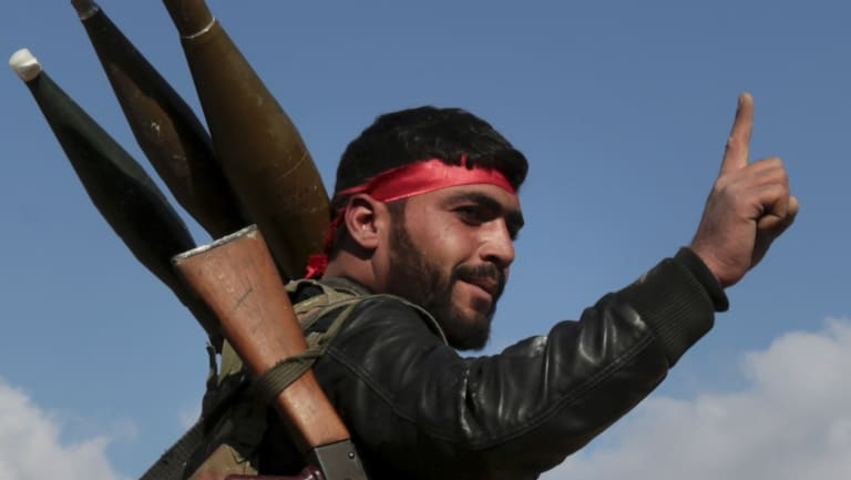 A pro-Turkey Syrian fighter waves on Bursayah hill, which separates the Kurdish-held enclave of Afrin from the Turkey-controlled town of Azaz, Syria.