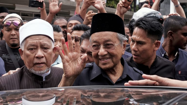 Malaysian Prime Minister Mahathir Mohamad, centre, waves to crowds leaving National Mosque after performing Friday prayers in Kuala Lumpur.