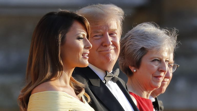 President Donald Trump, second from the right, smiles as he listens to first lady Melania Trump, far left, speak as they stand with British Prime Minister Theresa May at Blenheim Palace.