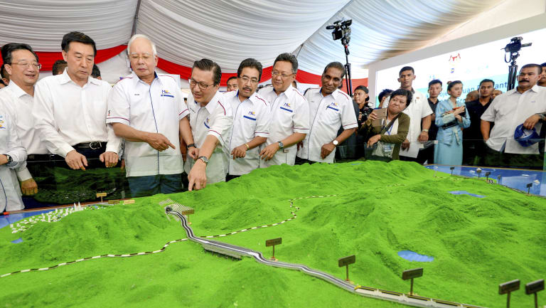 Former Malaysian prime minster Najib Razak, third from left, looks at models of the East Coast Rail Link.