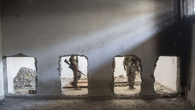 Members of the Syrian Democratic Forces (SDF) walk inside the stadium that was the site of Islamic State fighters' last stand in the city of Raqqa in October.