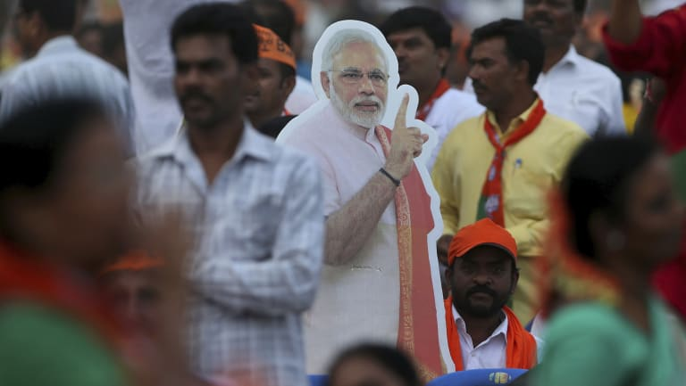 A cut-out of Indian Prime Minister Narendra Modi stands amidst the crowd during an election campaign rally in Bangalore.