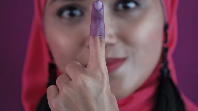 A Malaysian woman shows her inked finger after casting her ballot during the voting day of general elections on Wednesday.
