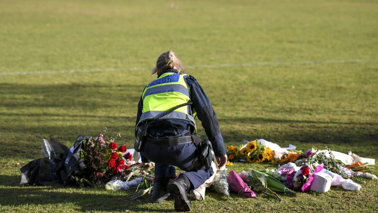 A female police officer lay flowers at the scene where Eurydice Dixon's body was found.