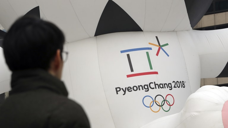 A man walks by the official emblem of the 2018 Pyeongchang Olympic Winter Games, in Seoul, South Korea.
