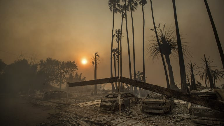Smoke rises behind a destroyed apartment complex in December 2017 after a wildfire burnt through Ventura, California.