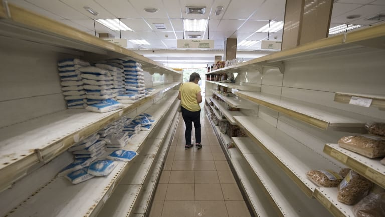 A customer moves along empty shelves as she shops for groceries at a supermarket in Caracas, Venezuela.