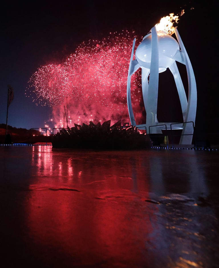 Fireworks explode behind the Olympic flame during the opening ceremony of the 2018 Winter Olympics in Pyeongchang, South Korea.