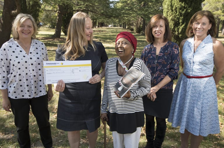 Singed Sisters Karen Downing, Chandani Prammer, Liz Tilley and Julie Pham, donate the proceeds of their cookbook to the YWCA through executive director Frances Crimmins.