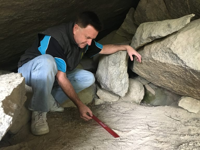 Greg Shaw measures the mystery left footprint with a ruler.