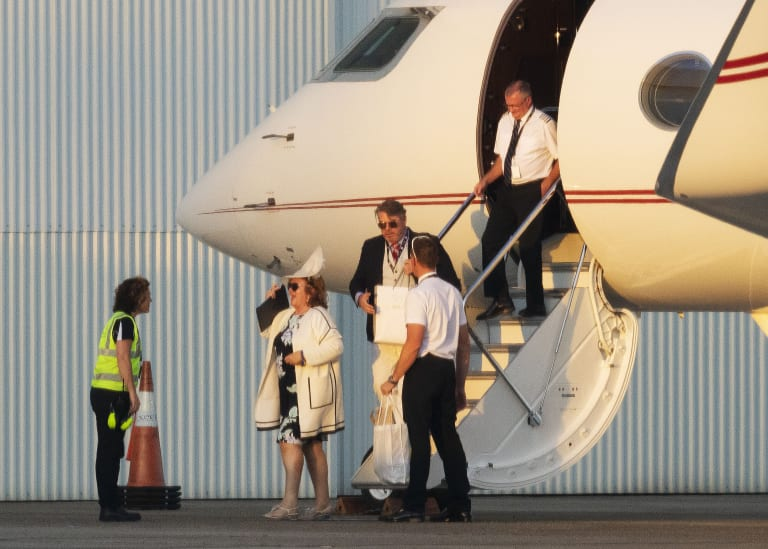 Gina Rinehart disembarks her private jet in Sydney after touching down in all her racewear finery with her entourage in tow.