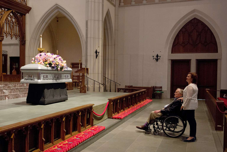 Former President George HW Bush looks at the casket of his wife.