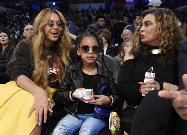 Tiny girl, grand tastes ... Blue Ivy (centre) at the basketball with her mother, Beyonce (left), and grandmother, Tina Knowles.