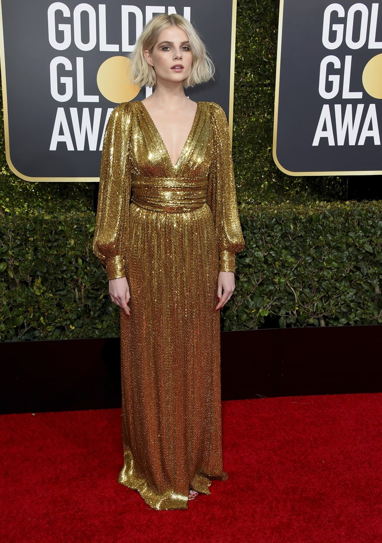 Lucy Boynton arrives at the Golden Globe Awards resplendent in gold.