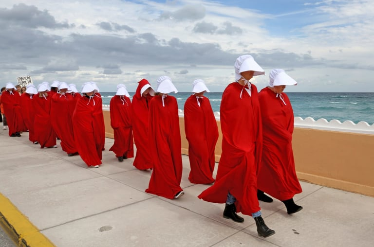Protesters dressed as handmaids march in protest of Donald Trump near his Mar-a-Lago home on Florida's east coast on Saturday, January 20, 2018.