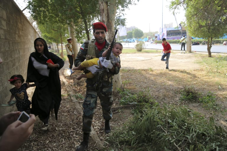 Iranian army member carries a child away from the shooting scene.