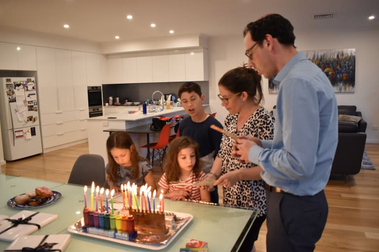 """Joshua, his wife Kirsten and their three children chant blessings just after lighting six candles to signify the """"sixth"""" day of Hanukkah."""