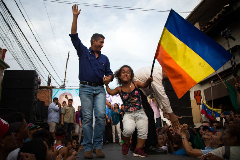 Henri Falcon, presidential candidate for the Progressive Front Party, left, arrives on stage during a campaign rally in Caracas, Venezuela, on Monday.