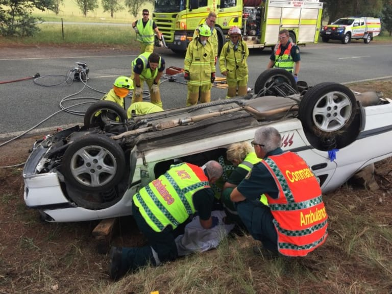 Ambulance officers and firefighters attend a single-vehicle crash on Randwick St in Lyneham on Thursday, January 10, 2018.