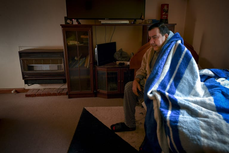 Princes Hill public housing resident Albert Rizk rugs up as he waits for his potentially-deadly heater to be replaced.