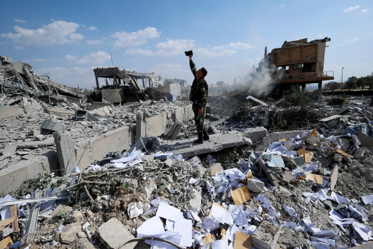 A Syrian soldier films the damage of a site which was attacked by US, British and French military strikes.