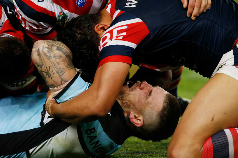 Josh Dugan hurts his neck in a tackle during Saturday's game between the Roosters and the Sharks.