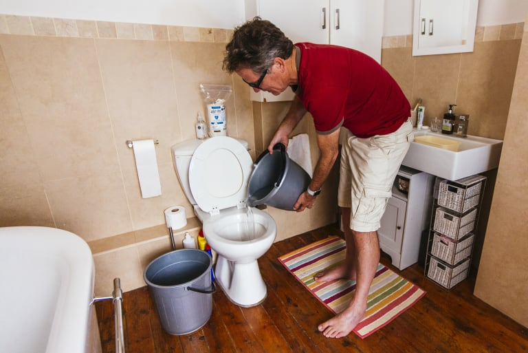 """John Viljoen, a Bloomberg reporter, fills his toilet with used shower water, also known as """"grey water"""" in Cape Town."""