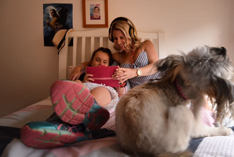 Keeley Haywood and her mum Kristy watch a video Keeley made on her iPad.