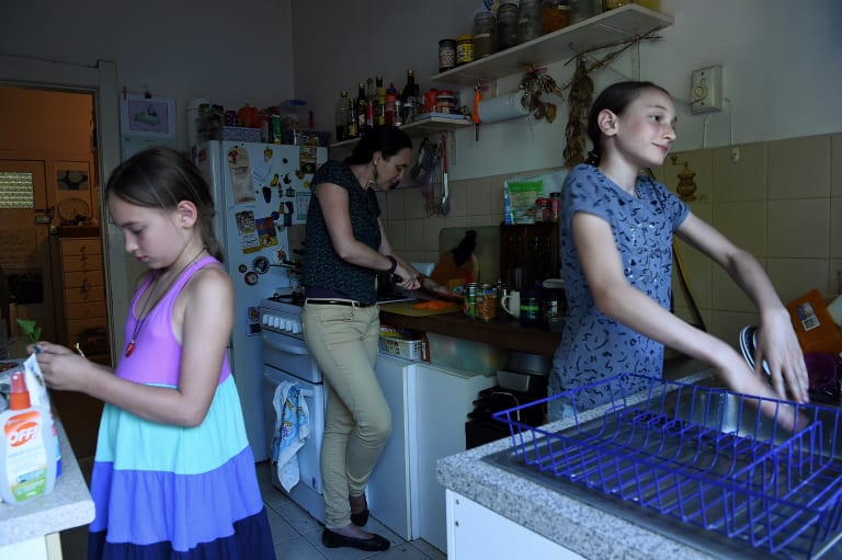 Maya Ruys 10 (left) and her sister Adelle Ruys 12 (right) in the kitchen with their mother Claire Boswell-Ruys (centre) in the apartment the family rents in Randwick, Sydney.