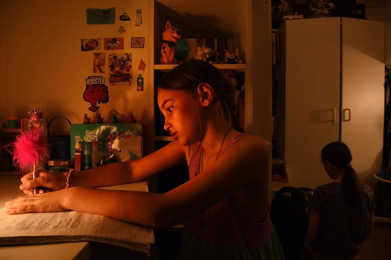 Maya Ruys 10 (left) and her sister Adelle Ruys 12 (right) do their homework in the bedroom all three children share in the apartment the family rents in Randwick, Sydney.