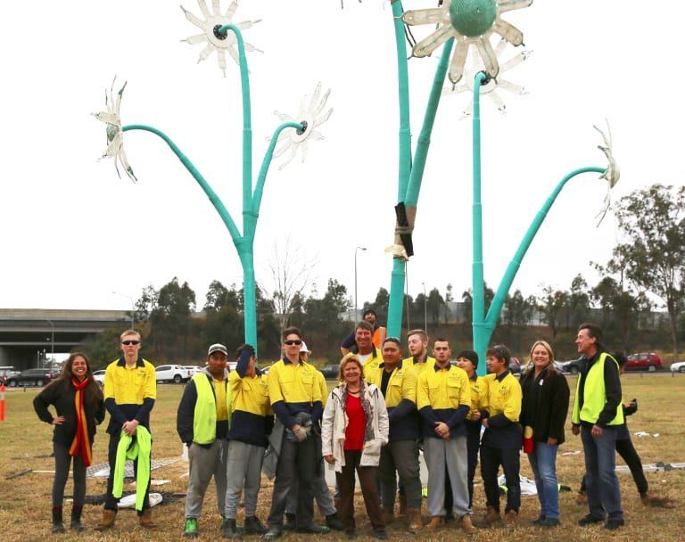 Artist Sharyn Egan (centre) and architect Linda Kennedy (left) with the crew from Productivity Bootcamp, Quakers Hill, in front of a sculpture called the <em>Flannel Flower.</em>