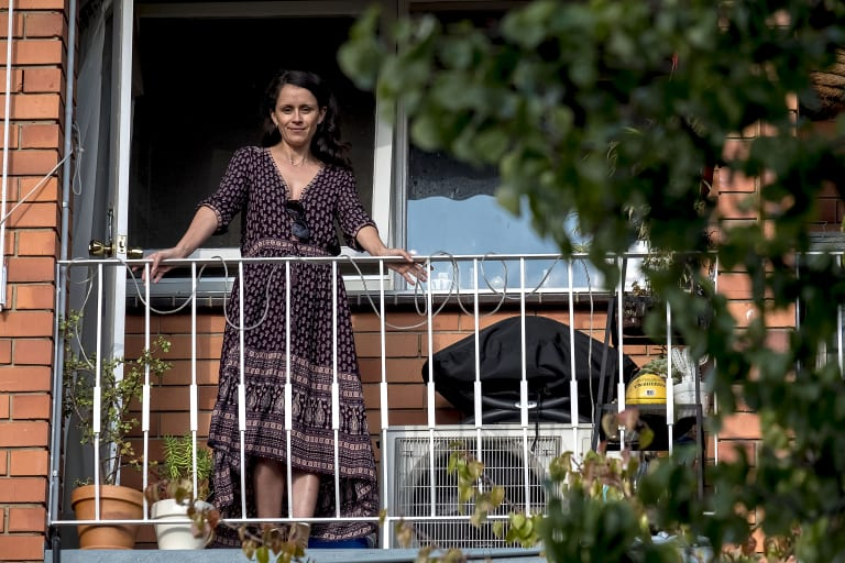 Cassandra Huett stands on her balcony overlooking one of the trees the corellas attacked.