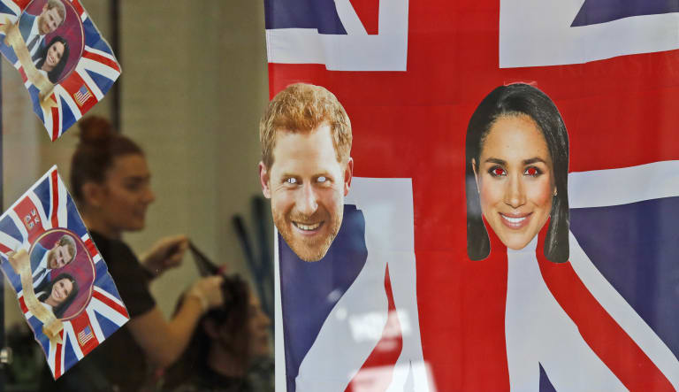 A woman gets a haircut as the Windsor shop window is decorated with flags and pictures of Prince Harry and Meghan Markle.