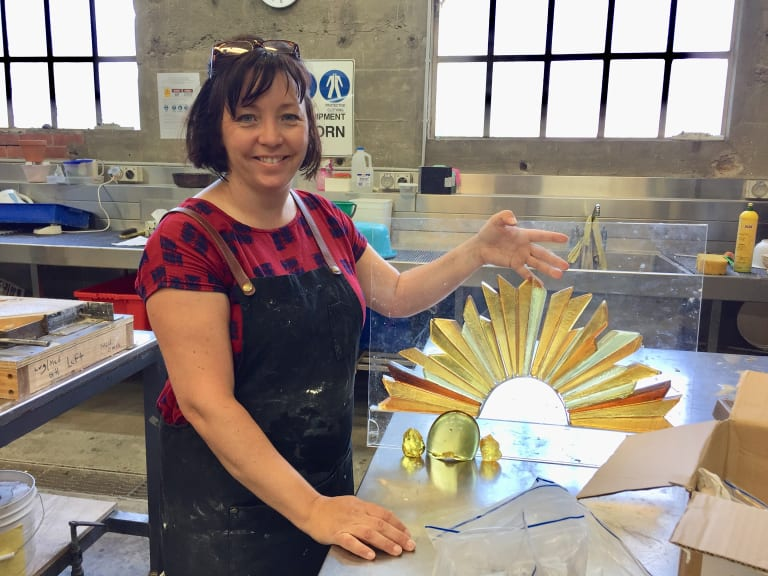 Canberra artist Lisa Cahill with a model of her Rising Sun sculpture which she made at the Canberra Glassworks.
