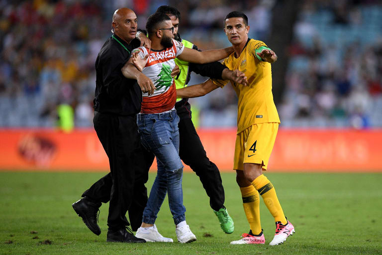 The attacker is captured by security when Tim Cahill from Socceroos reaches during the match.