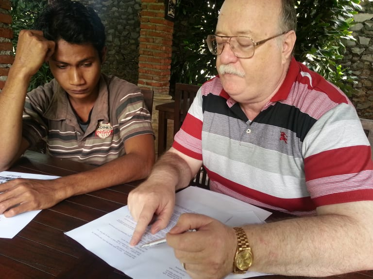 Colin Singer (right) explaining legal documents to Ali Jasmin at a restaurant in Bandung, Indonesia, in 2014.