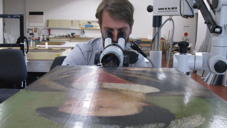 ANU academic Dr Matthew Brookhouse examining the portrait of Henry VIII.